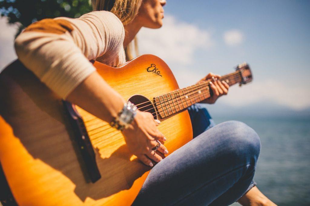 Vrouw speelt gitaar, omdat ze wil afvallen en neemt dit op op een geheugenkaart