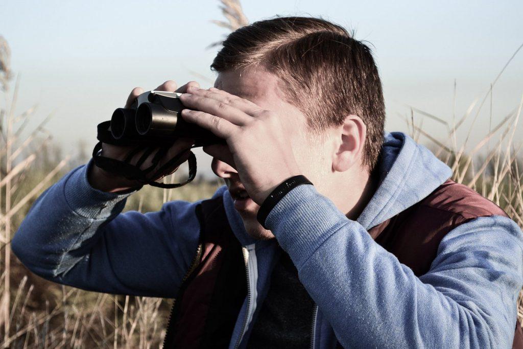 Een vogelspotter kijkt door een verrekijker