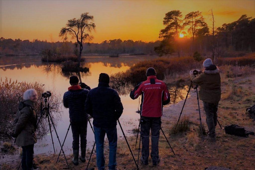 Groepje fotografen zijn de zonsondergang aan het fotograferen in een bos aan een meer.